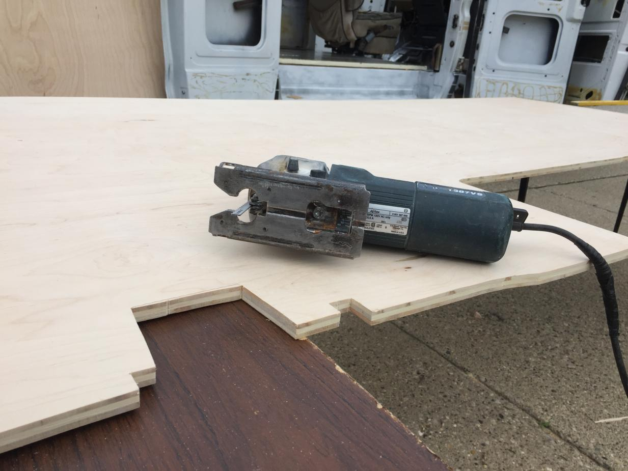 """Reused cardboard template, slightly modified to account for 1"""" height change from rigid board insulation (it grew a bit around the wheel wells, etc). Cutting the 1/2"""" birch subfloor with the jig saw."""