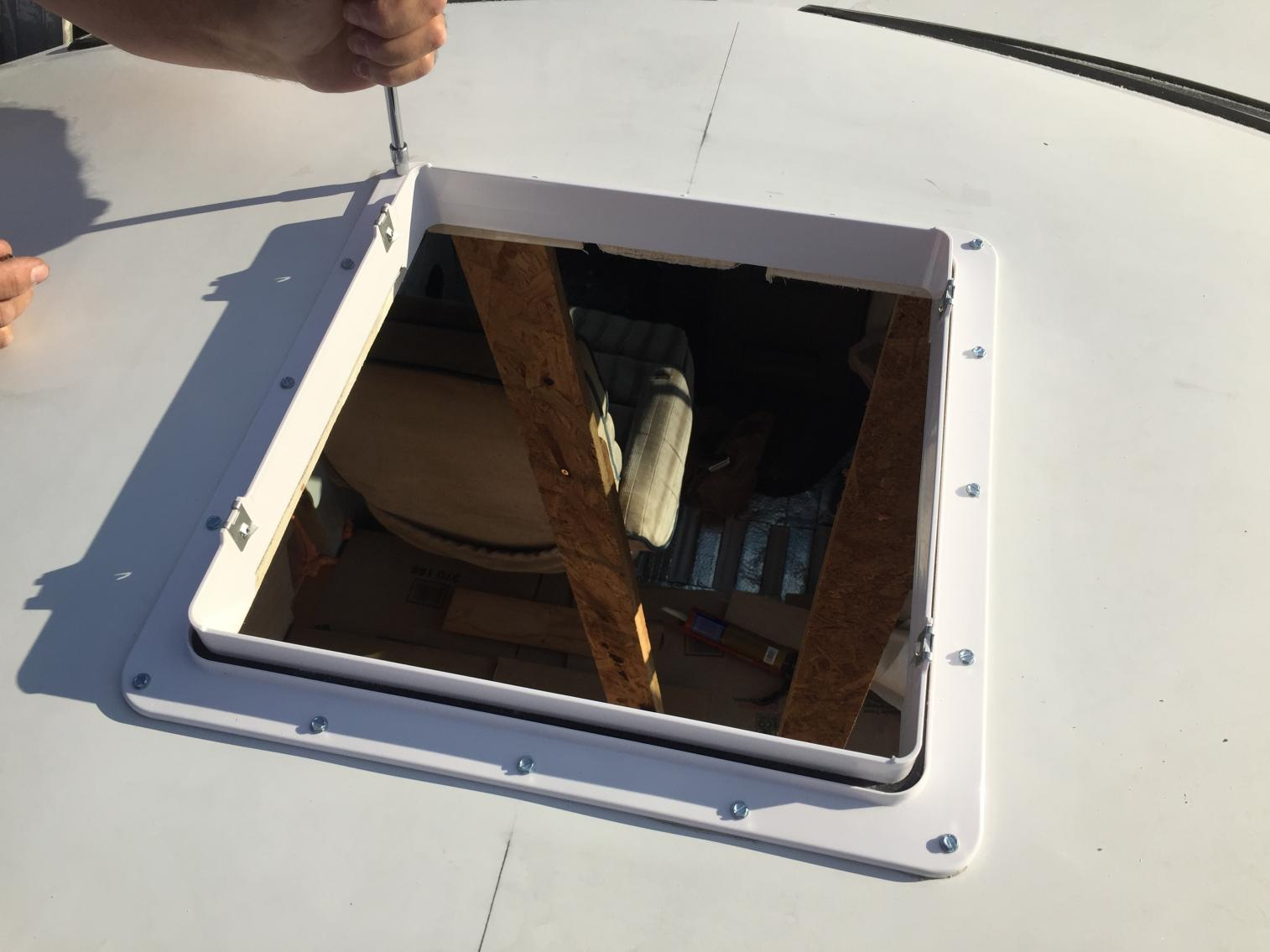 Installing MaxxAir MaxxFan Deluxe. Cut whole in fiberglass hightop roof. Screwed with hex screws with some 1/2 birch plywood for backing. Sealed with Dicor butyl tape and lap sealant.