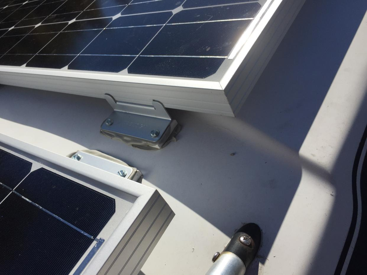 x3 Renogy 100 watt solar panels installed with Renogy Z brackets and plastic wedges underneath to level surface.