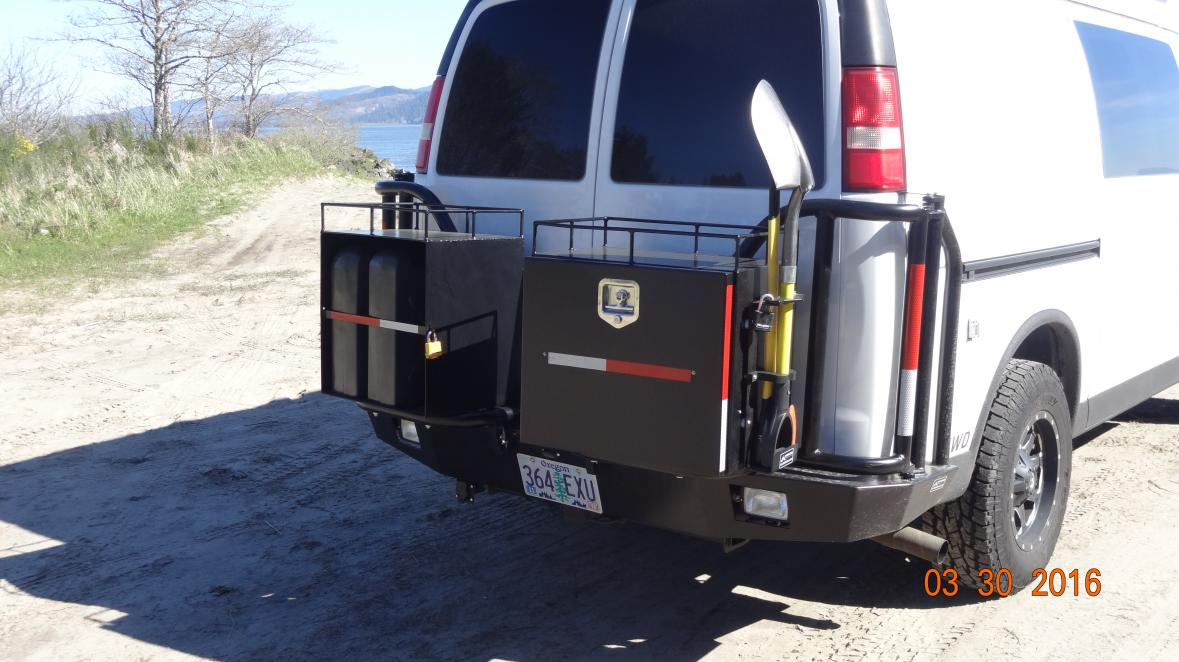 close up of rear Aluminess bumper. Galley/chuck box on curb side and 3 jerry can box on street side. Hella back up/camp lights in bumper.